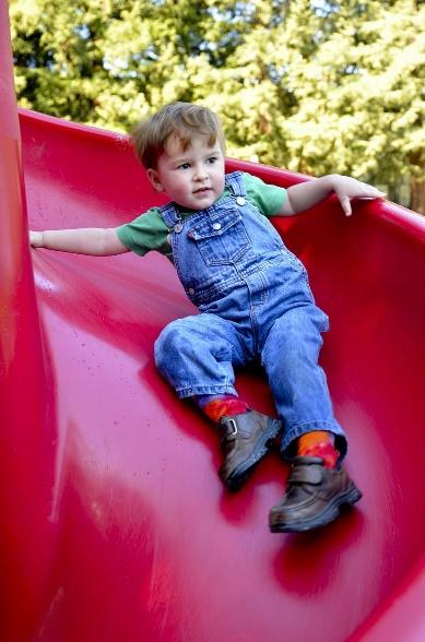 játszótér piros csúszda és kisfiú
